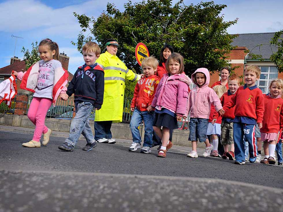 Pre-school children crossing the safely with Jolly Jesters staff